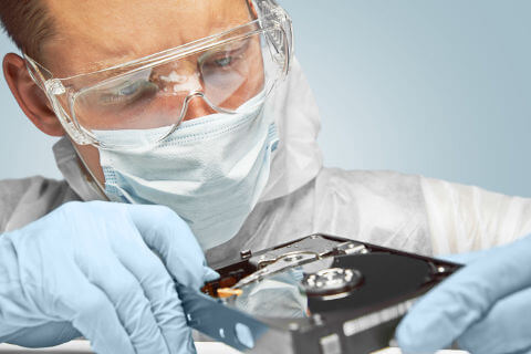 Lab worker examining hard drive