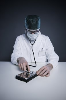 Doctor or Technician wearing a lab coat and stethoscope examining an hard disk
