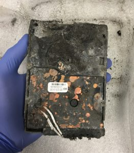 fire damaged drive held by gloved hand